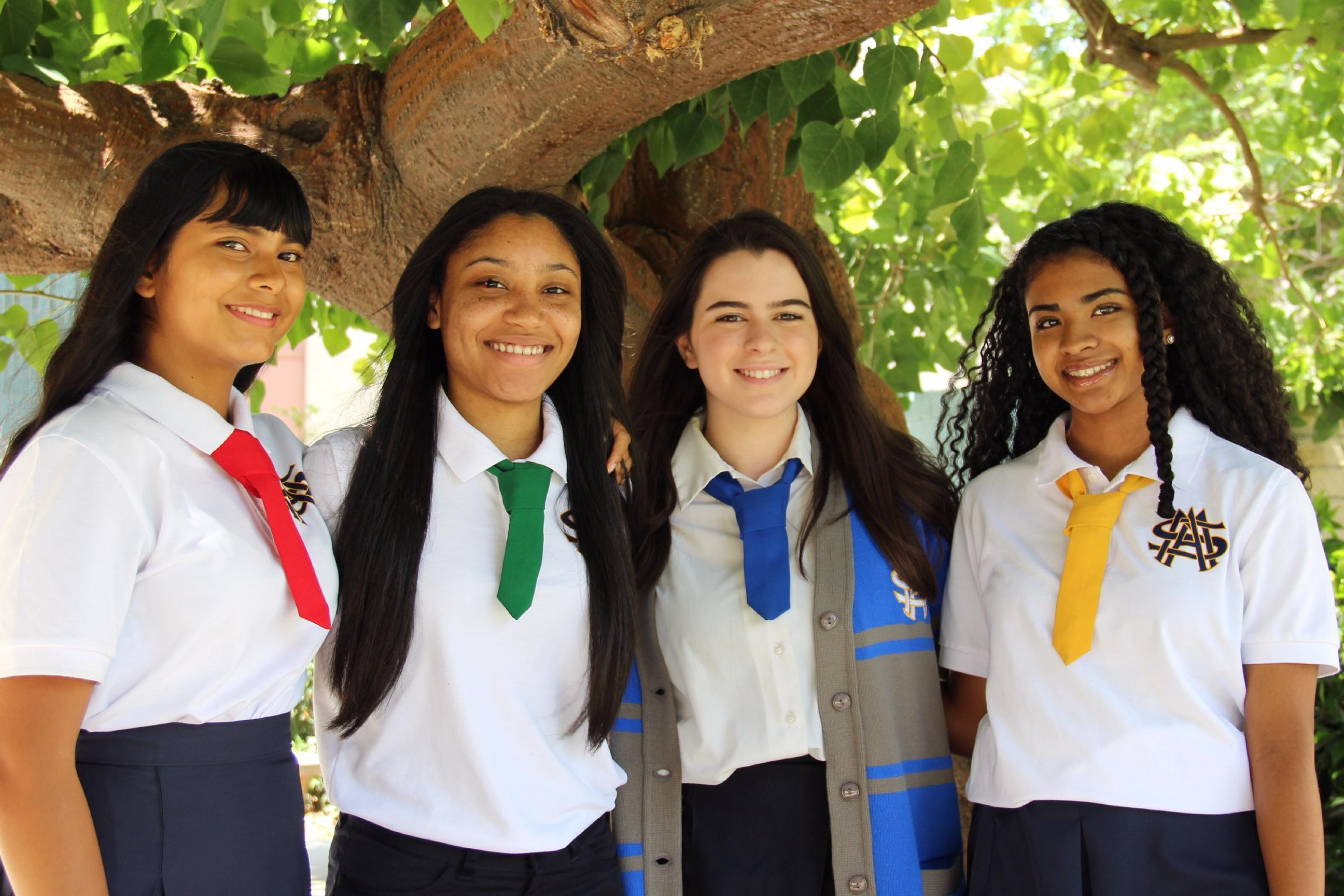 four students posing in front of a tree