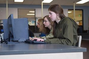 Three female students work on computer programing