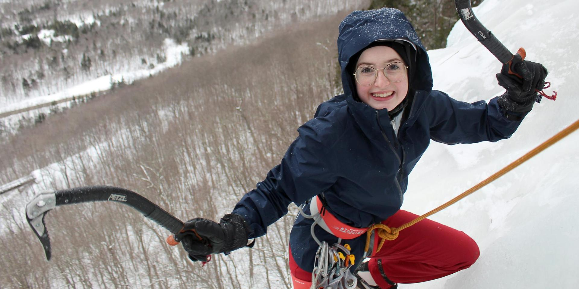 A student reaches the peak of an ice cliff in Franconia.