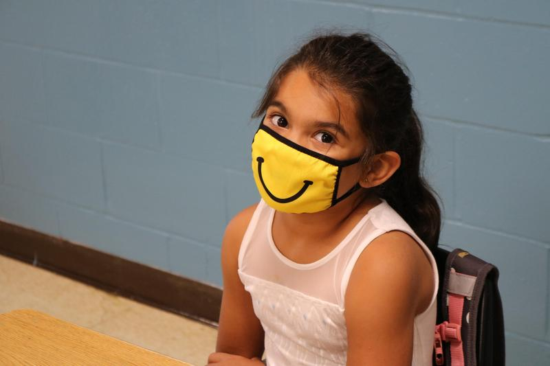 Girl in a smiley face mask.