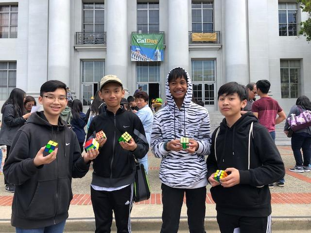 Four CCA students holding Rubik's cubes.