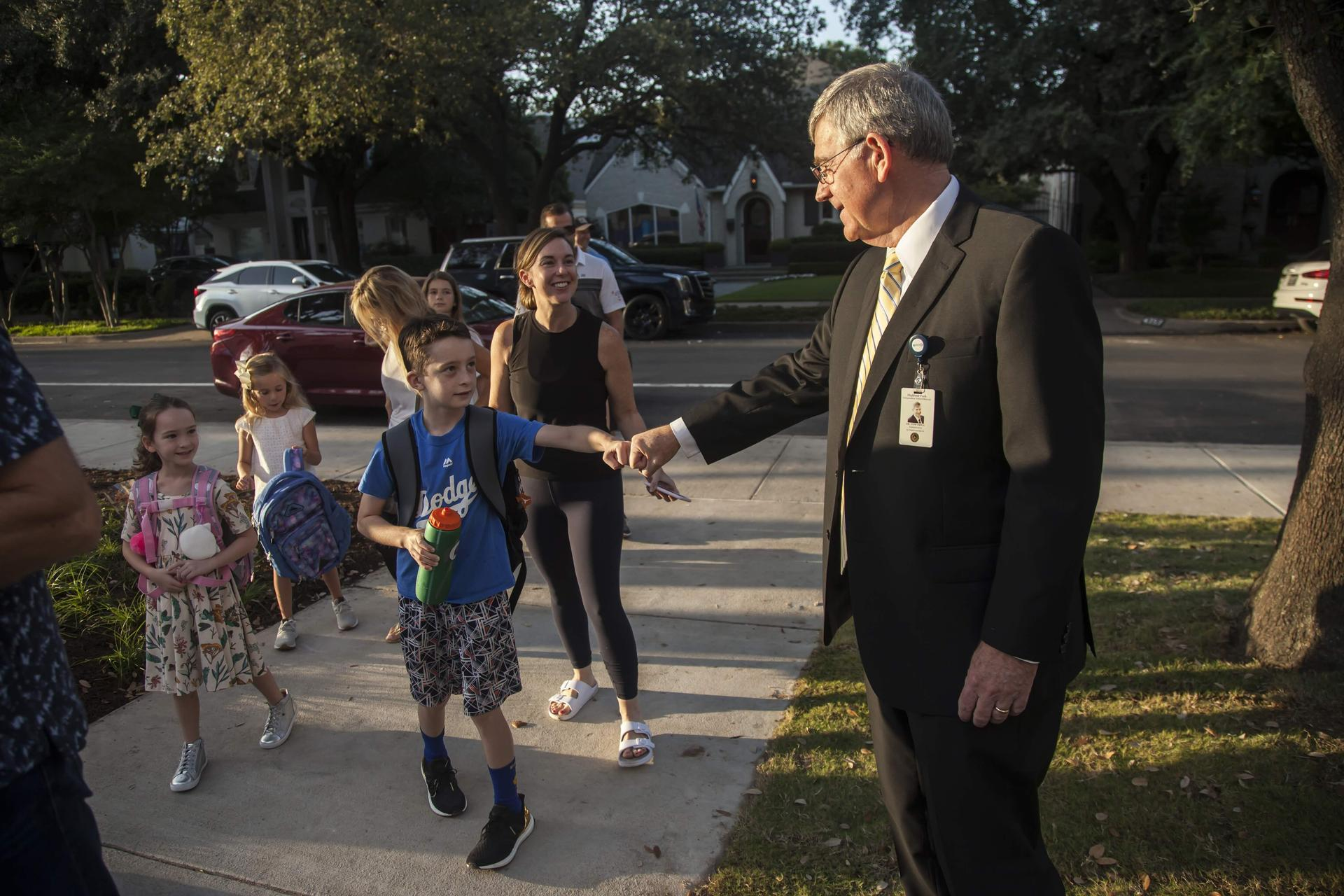 Dr. Trigg welcoming students with a fist bump on the first day of school.