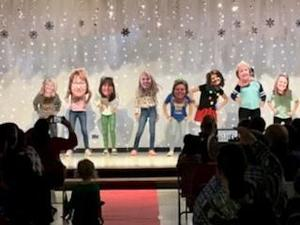 Fifth grade students with bobbleheads at Talent Show.