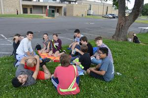 10 boys and girls sitting on a picnic blanket chatting and getting to know one another.