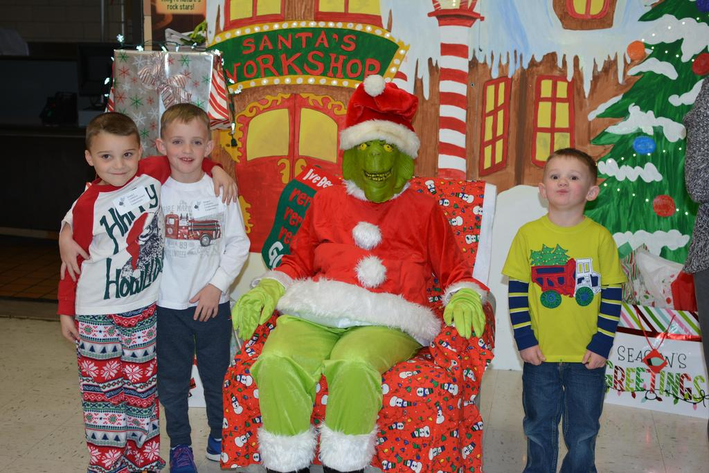 Teacher dressed in Grinch costume poses for pictures with students