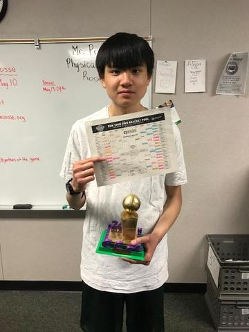 A student holding a trophy and a bracket for March Madness.