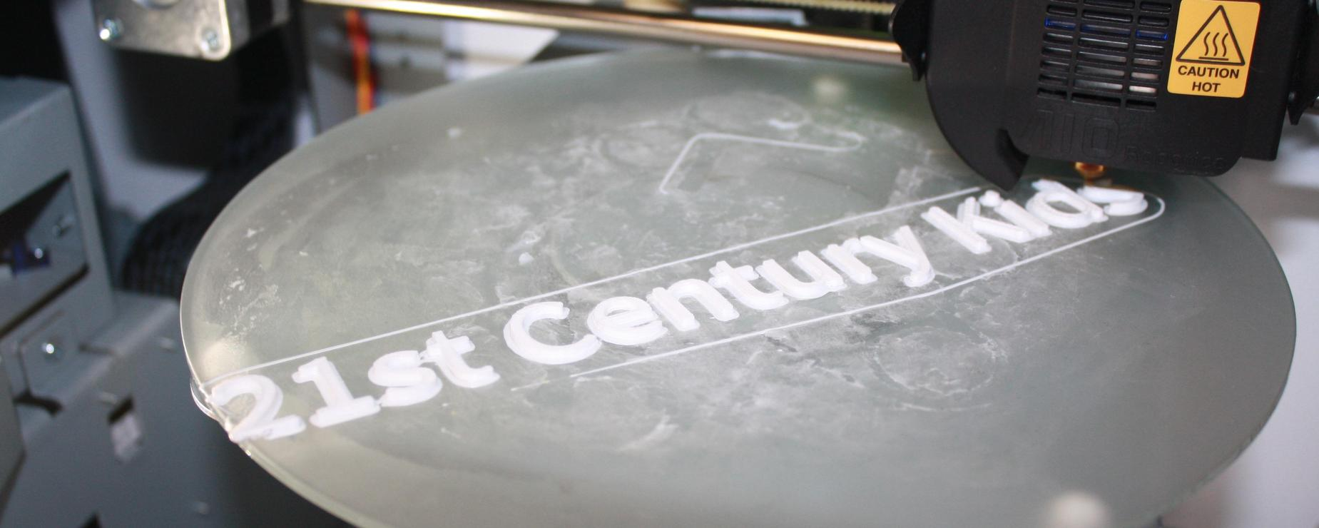 3D Printer printing out the 21st Century Kids logo