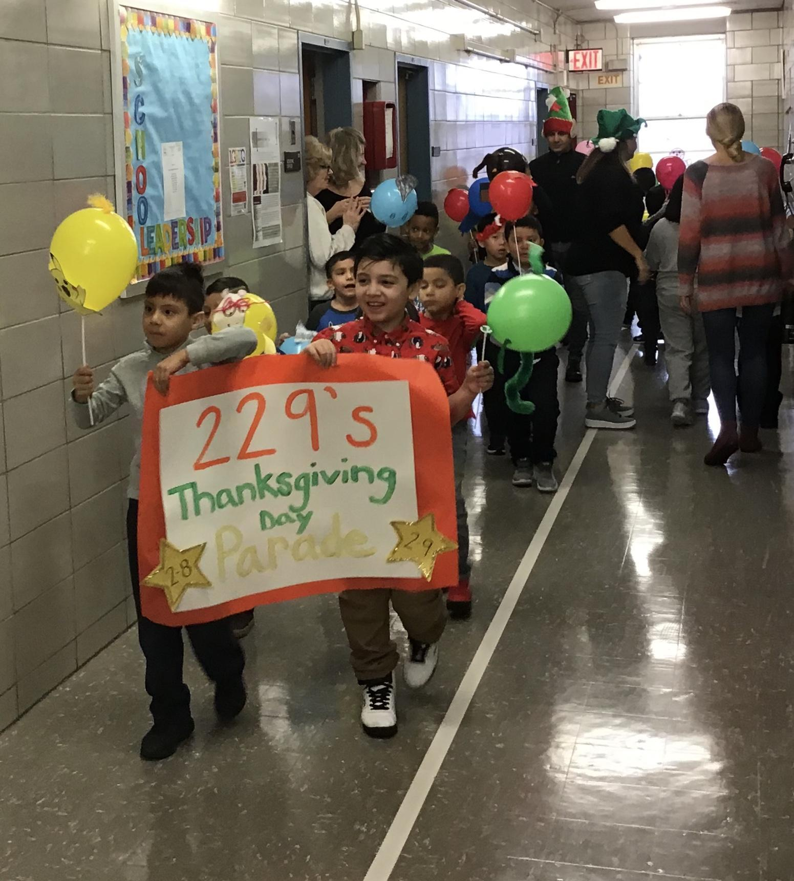 students parading in school hallway with balloons and sign