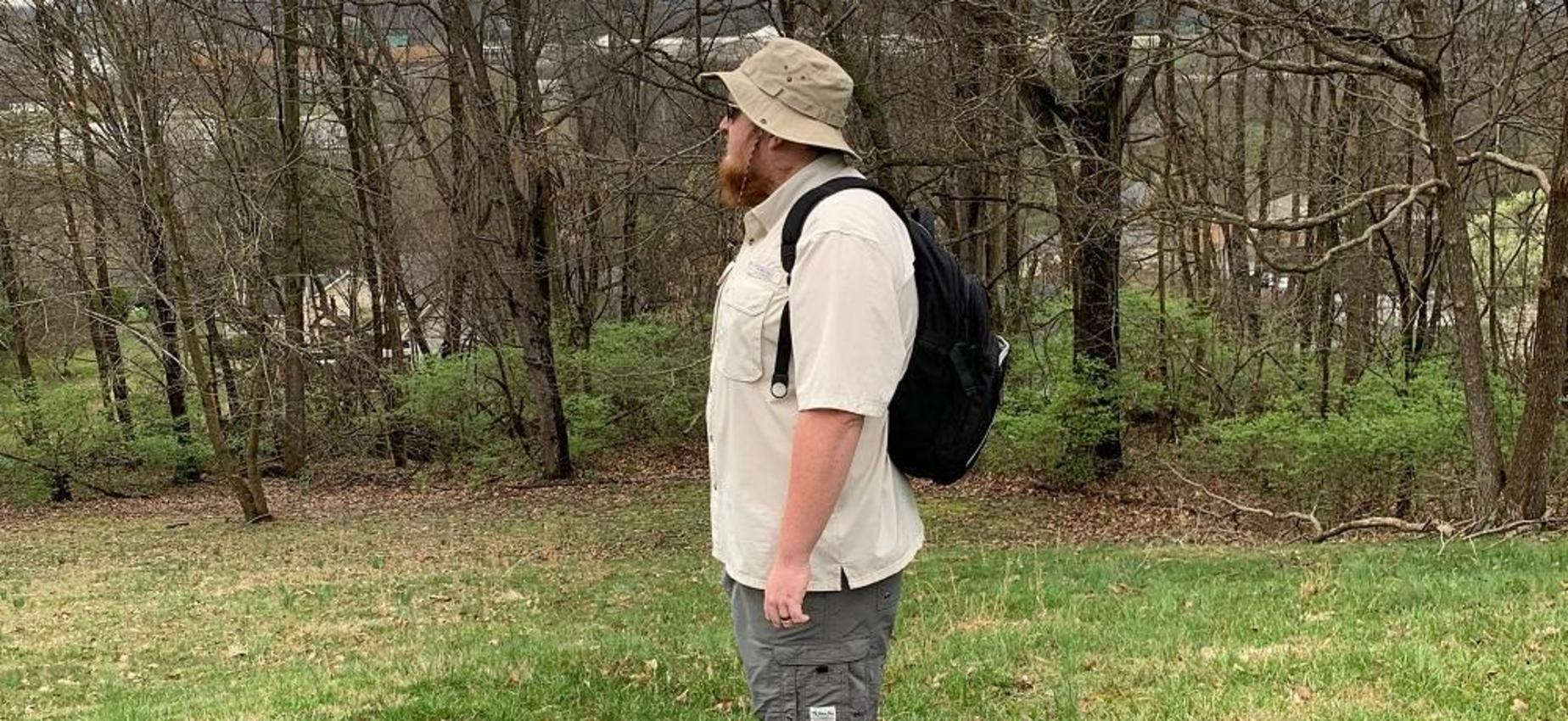 A man wearing a backpack stands in a wooded area.