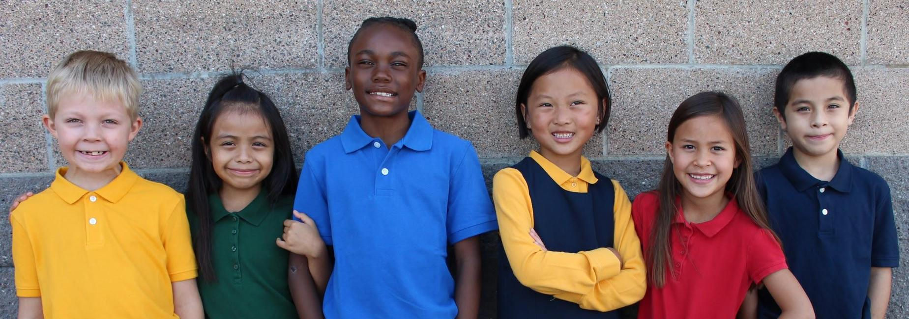6 CILA students in different uniform shirts smile for the camera