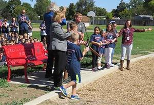 Children celebrate cutting the ribbon on their new bench.