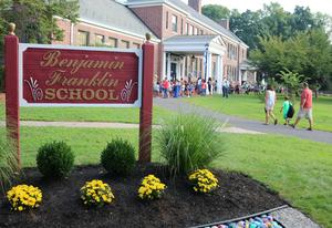 Franklin School sign in foreground; families arriving during first week of school in background.