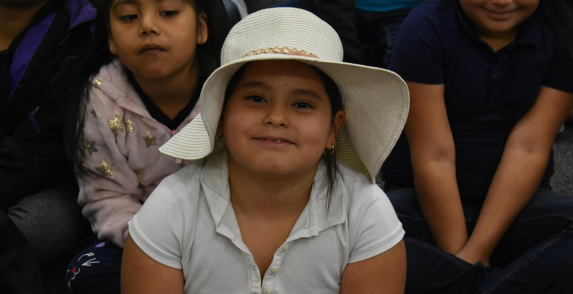 A little girl wearing a white floppy hat for hat day.