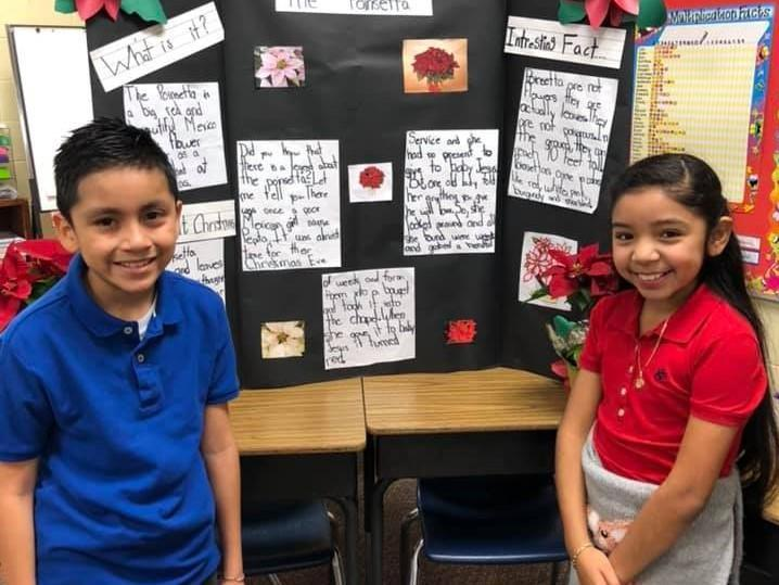 Two 4th grade students showing their Christmas Around the World display