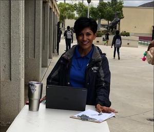 Lisa Ruiz standing at a table ready to check students into school.