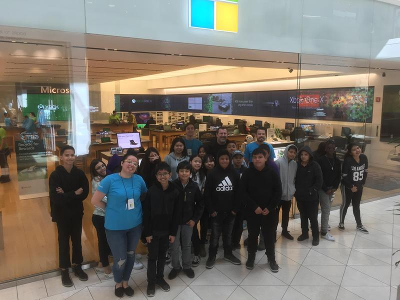 students and staff posing for a picture in front of the Microsoft store