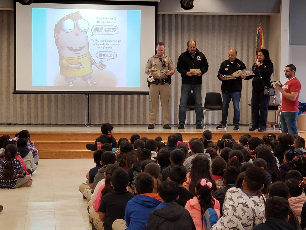 police officers and representatives of Shop with a Cop read Fly Guy book to students