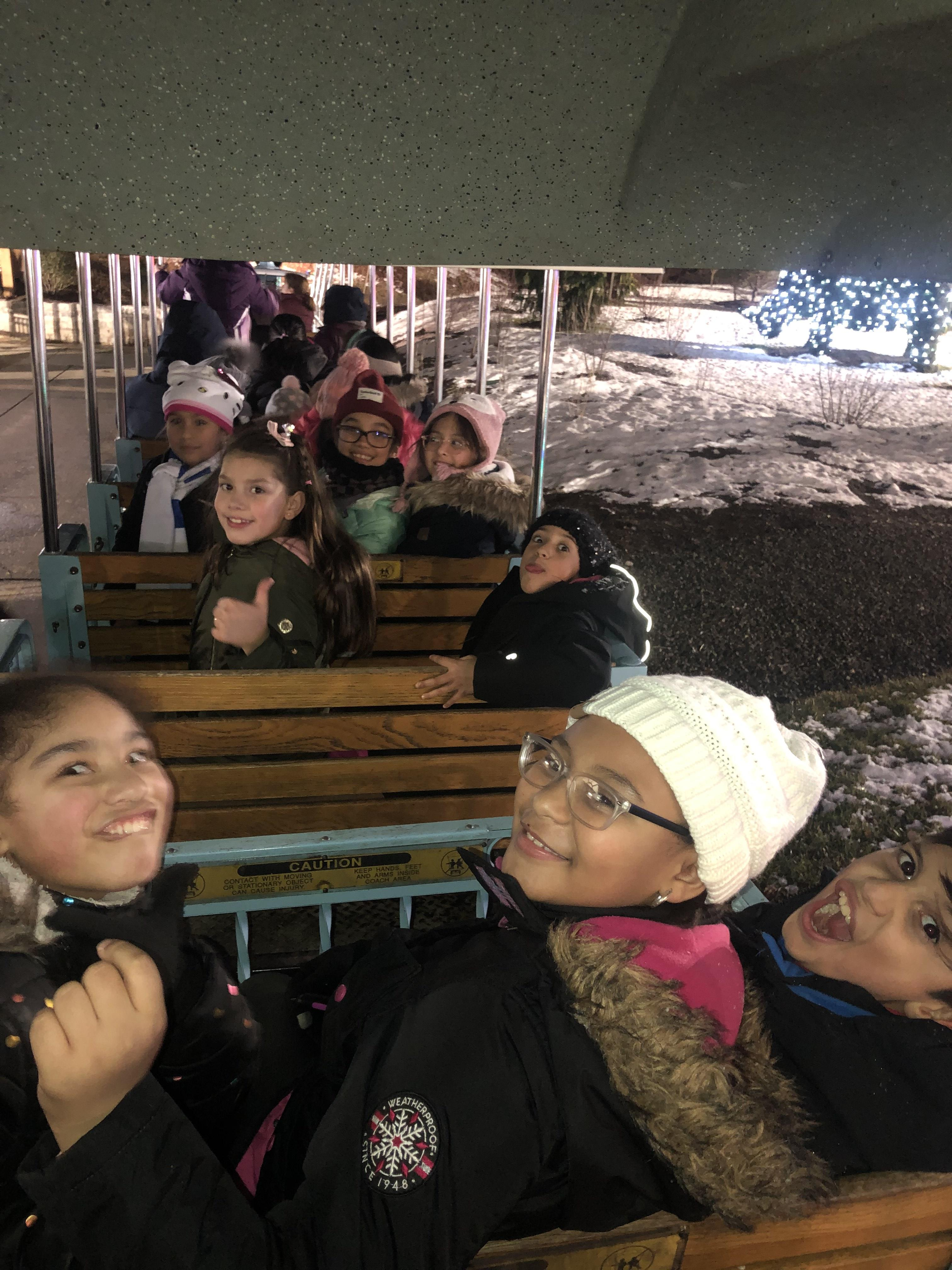 group of kids smiling while on the little red train