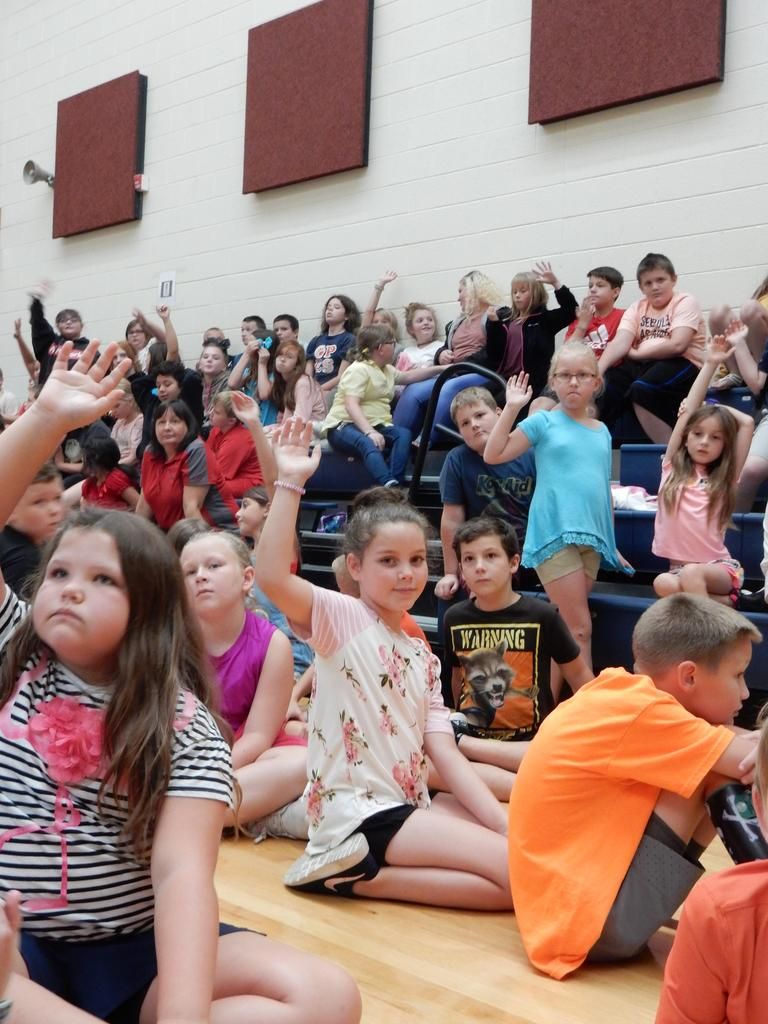 Students with hands raised to ask questions