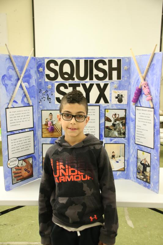 A second grader giving his invention convention project.