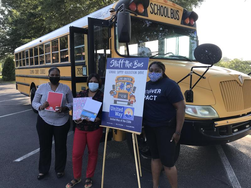 holding school supplies smiling in front of school bus