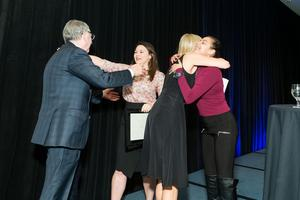 9th Annual Business Lunch - Janet & Clint Reilly receving hugs from alumnae and former Clinton Reilly Holdings CWSP workers