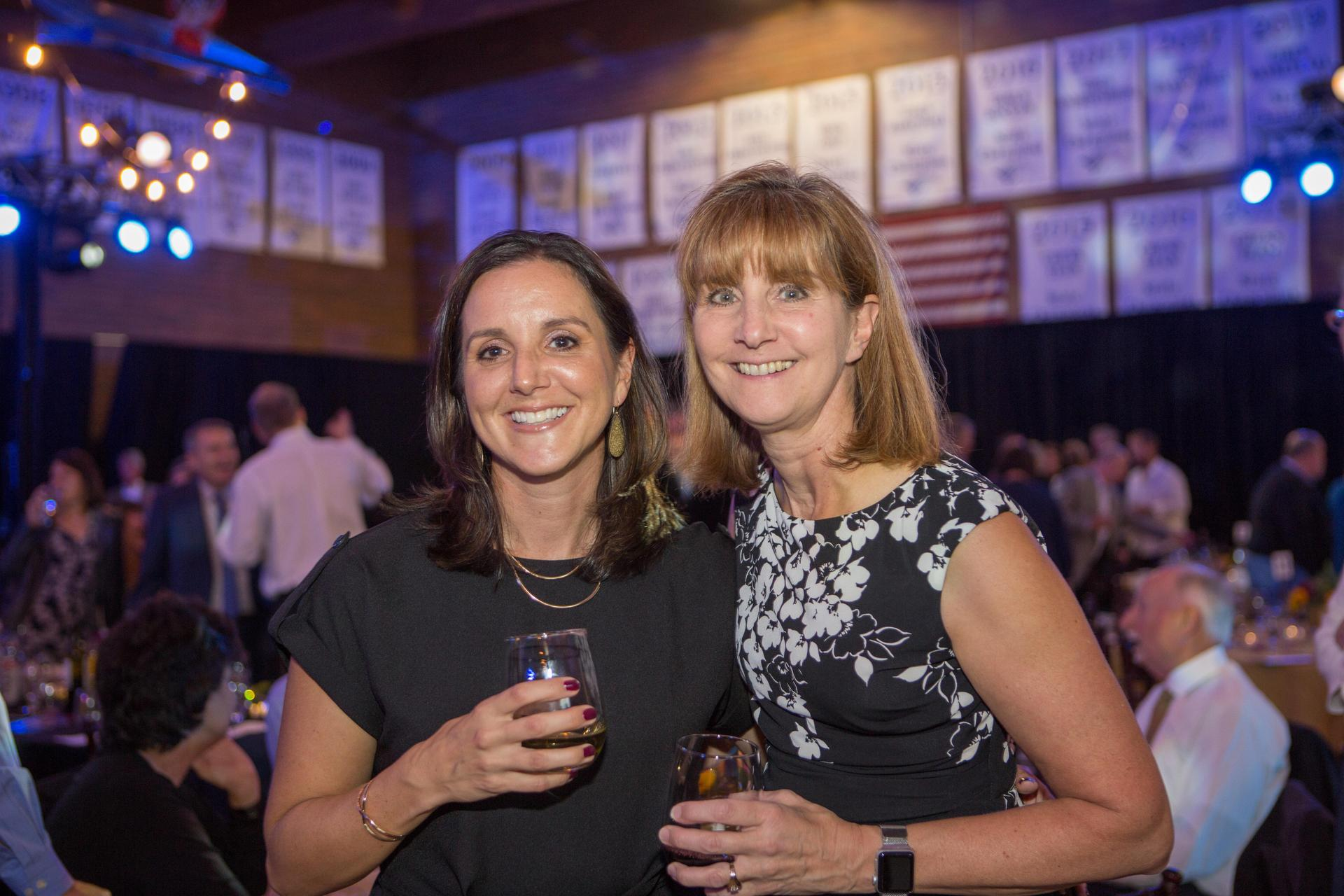 two women smile at event