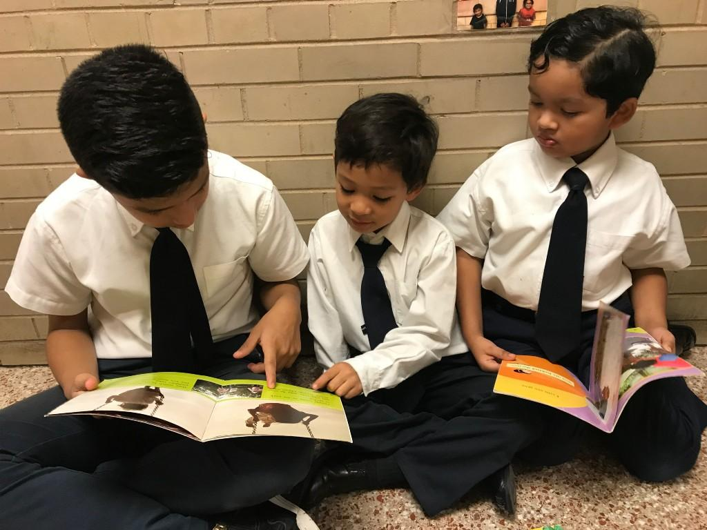 An older student helps younger students read
