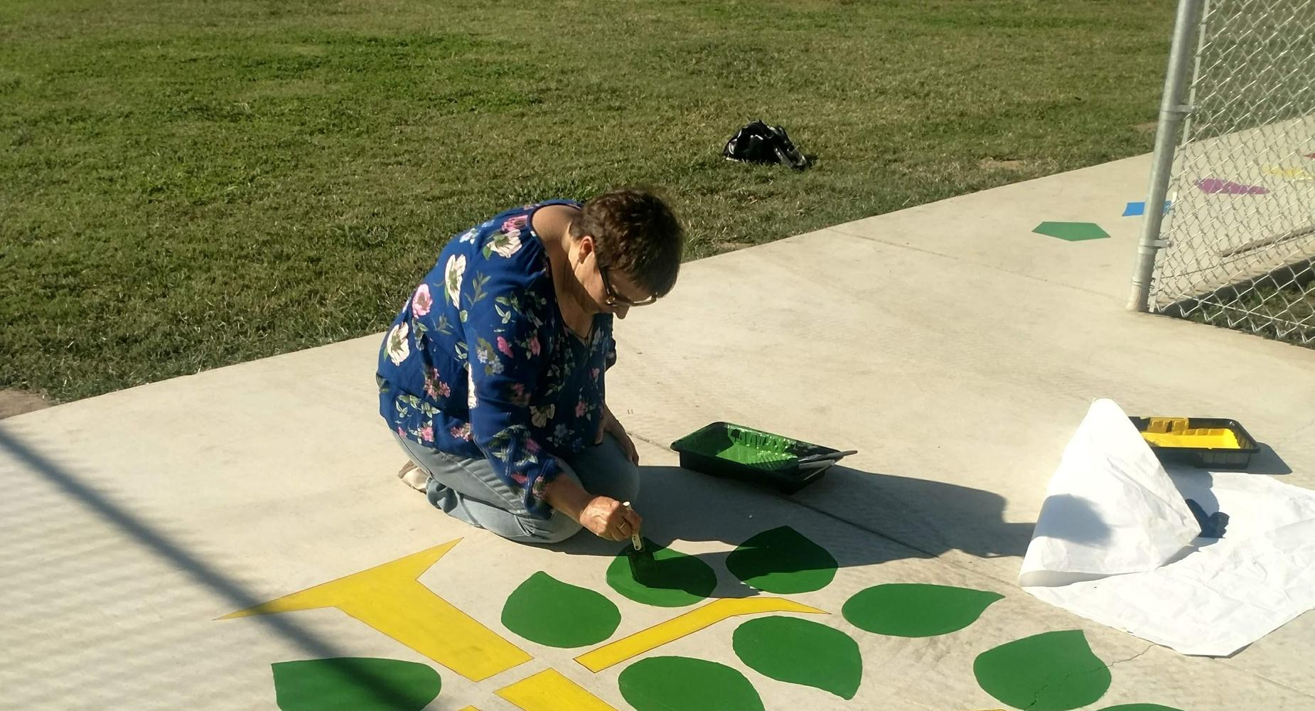 Mrs. Lantrip painting for the TK and Kindergarten Stencil project.