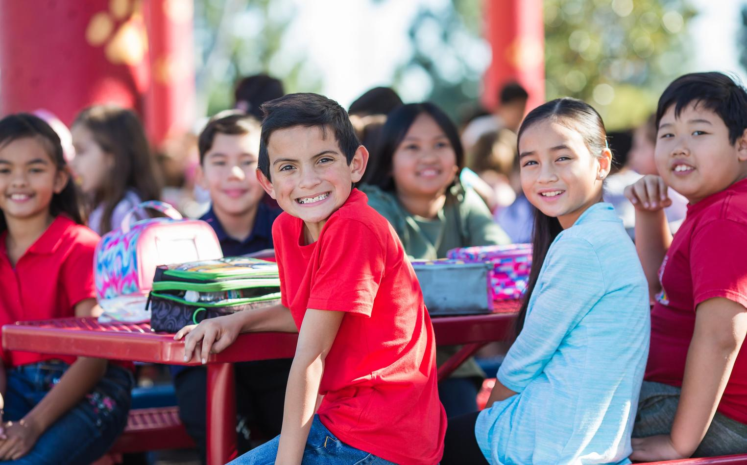 A group of young students smile for the camera at a lunch bench.