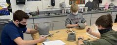 Three art students work on pottery at a table