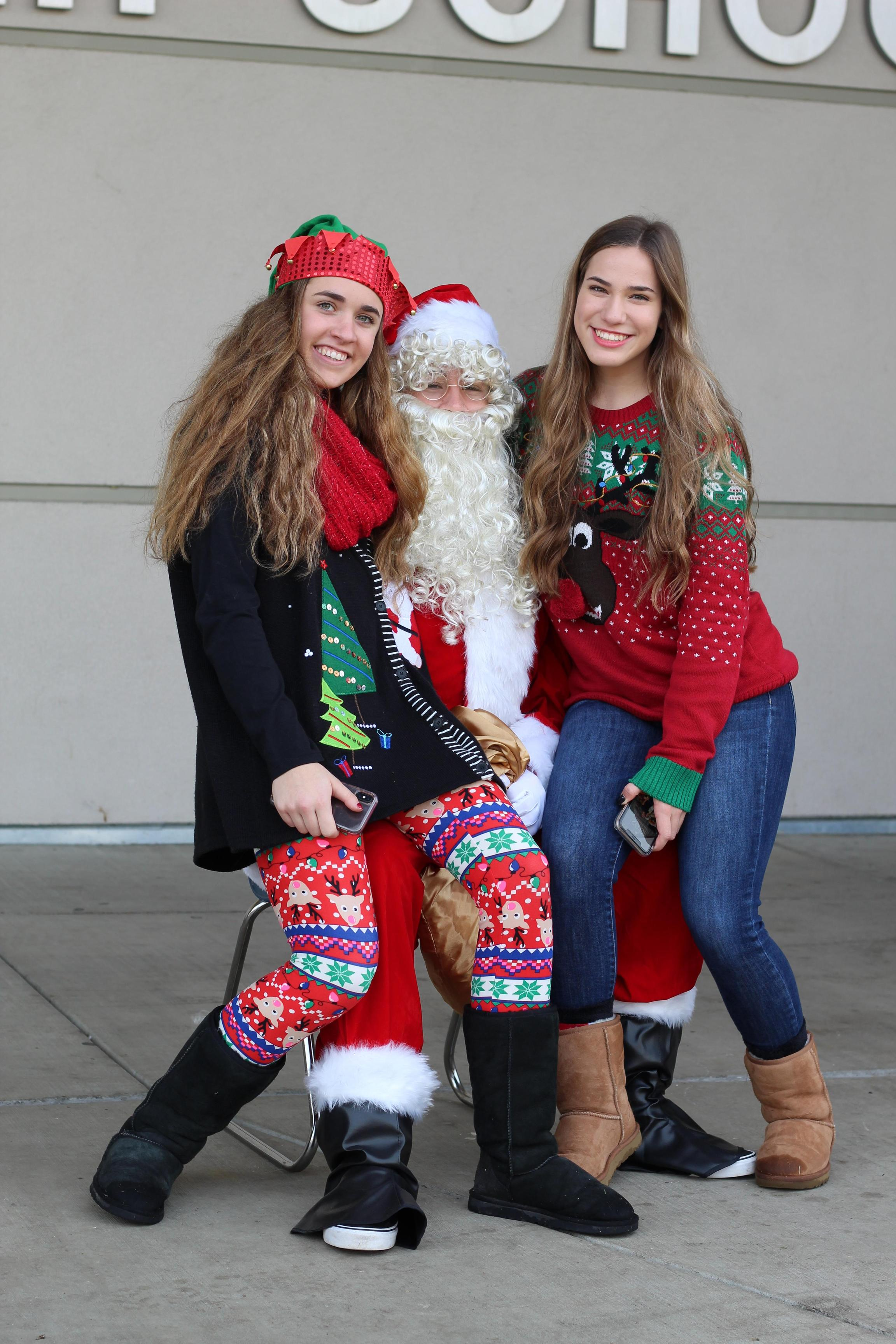 Adriana Felsinger and Christina Fuller sit on Santa's lap