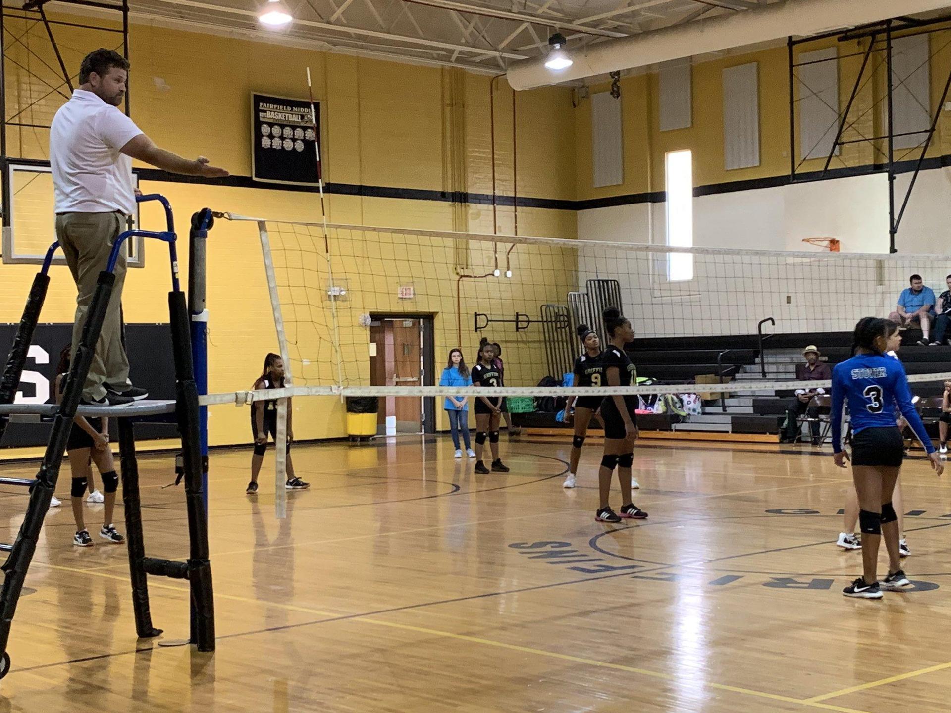 Girls' Volleyball Team behind the volleyball next.