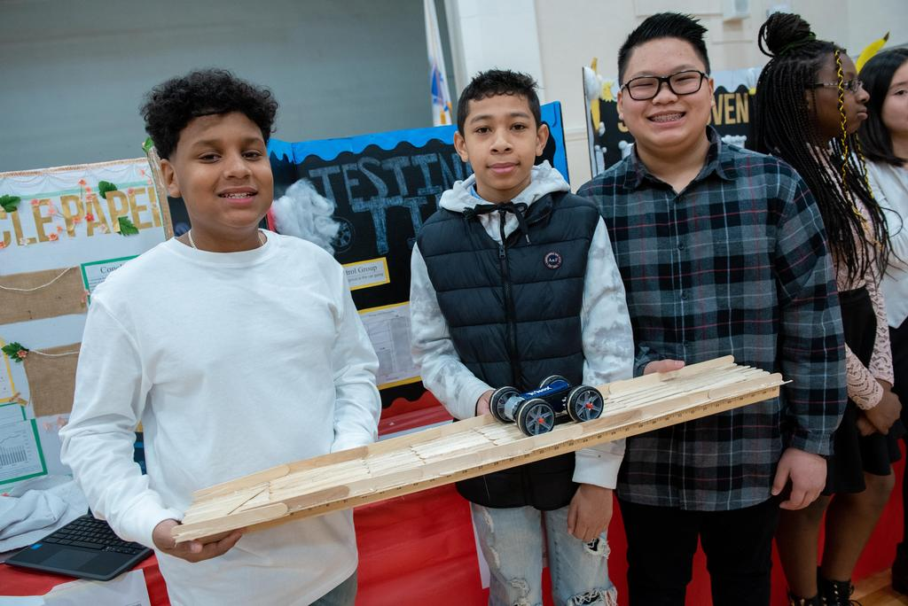 Three students hold a wooden track and a four-wheeled device they made for their project