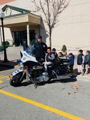 young boy on the ucpd motorcycle with officer next to him