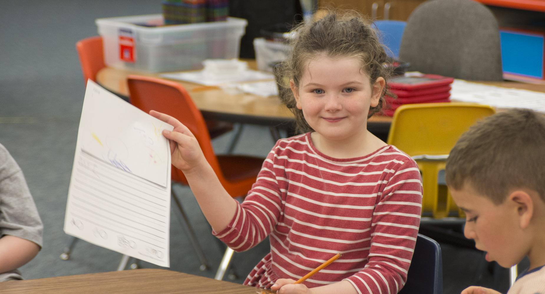 Girl holds up worksheet and smiles.