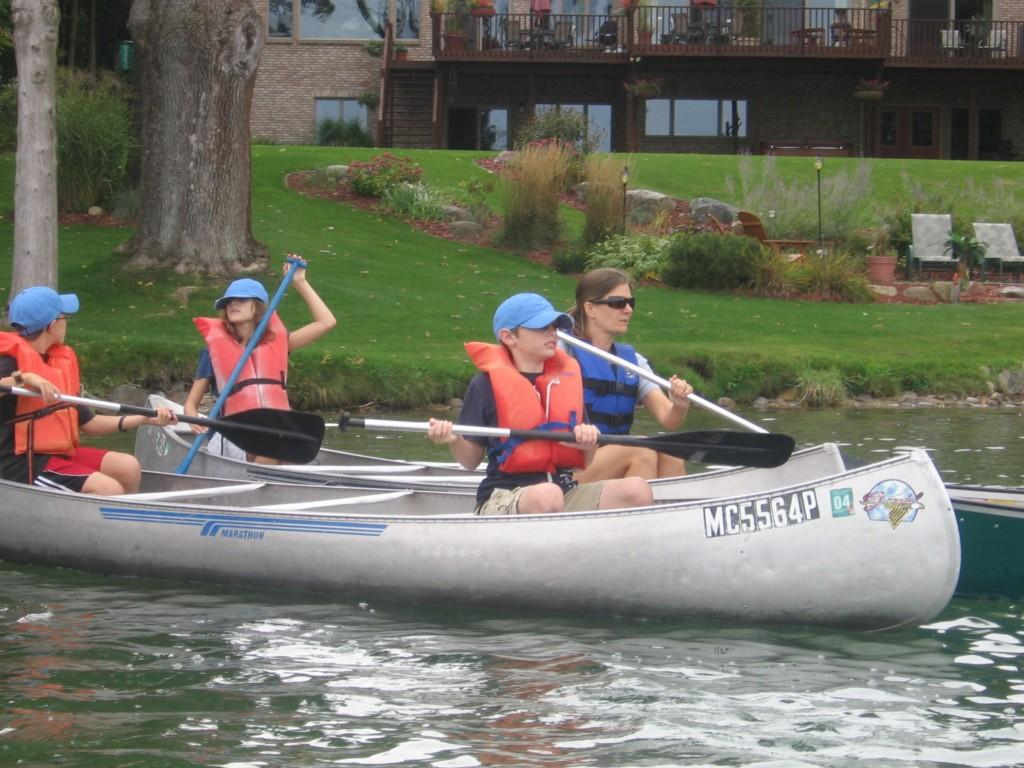students rowing boat on lake