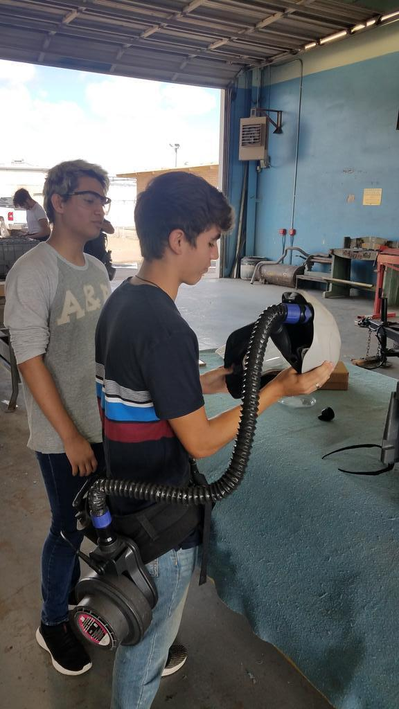 student about to put on helmet with connected air hose