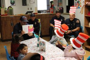 Firefighter reading to children in babysitting.