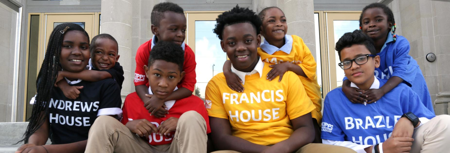 4 KLA and 4 KLP students posing on the steps of the school wearing house T-shirts