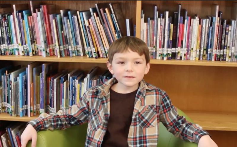 Child sitting in front of bookshelf