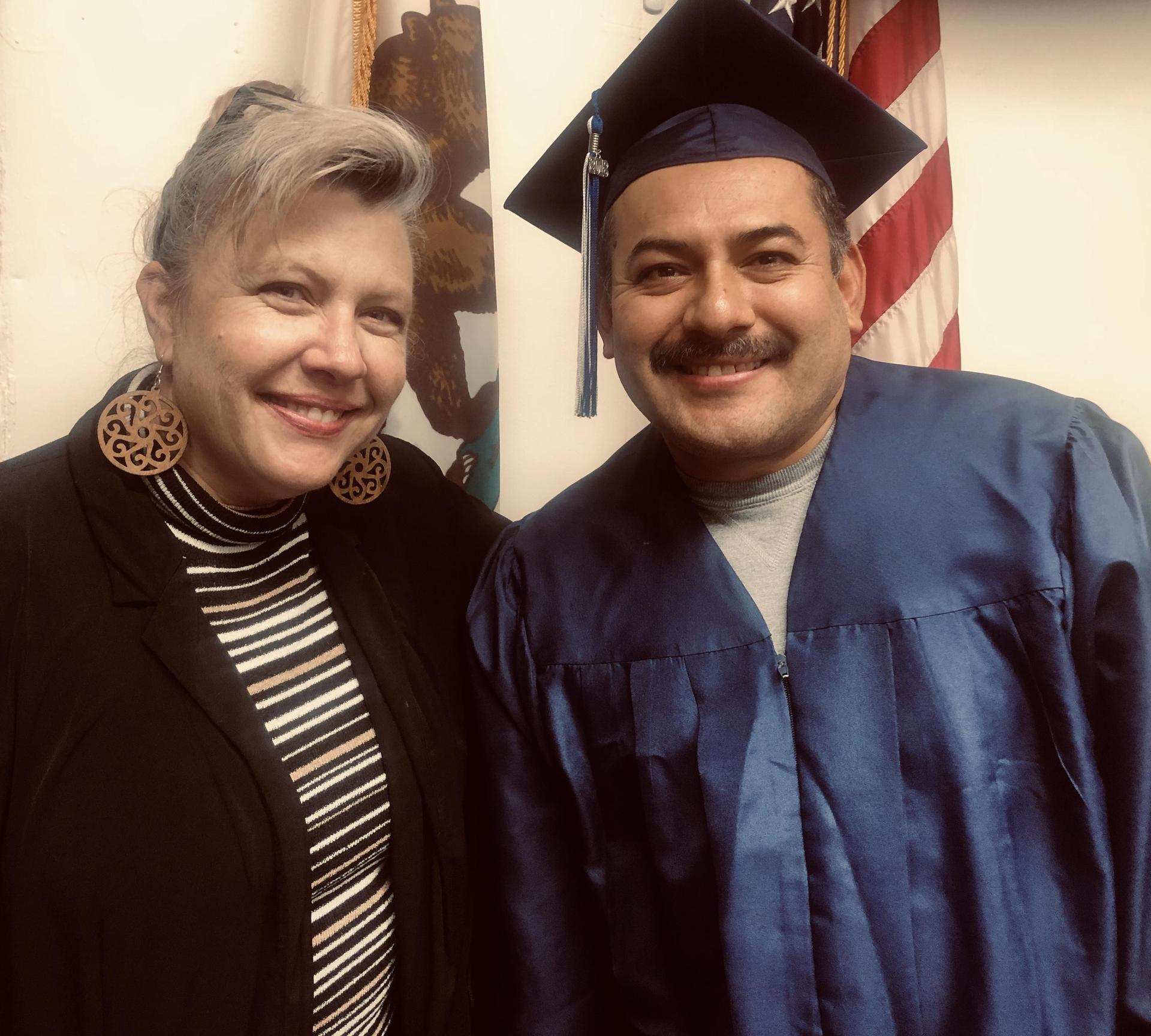 student in cap and gown with adminstrator