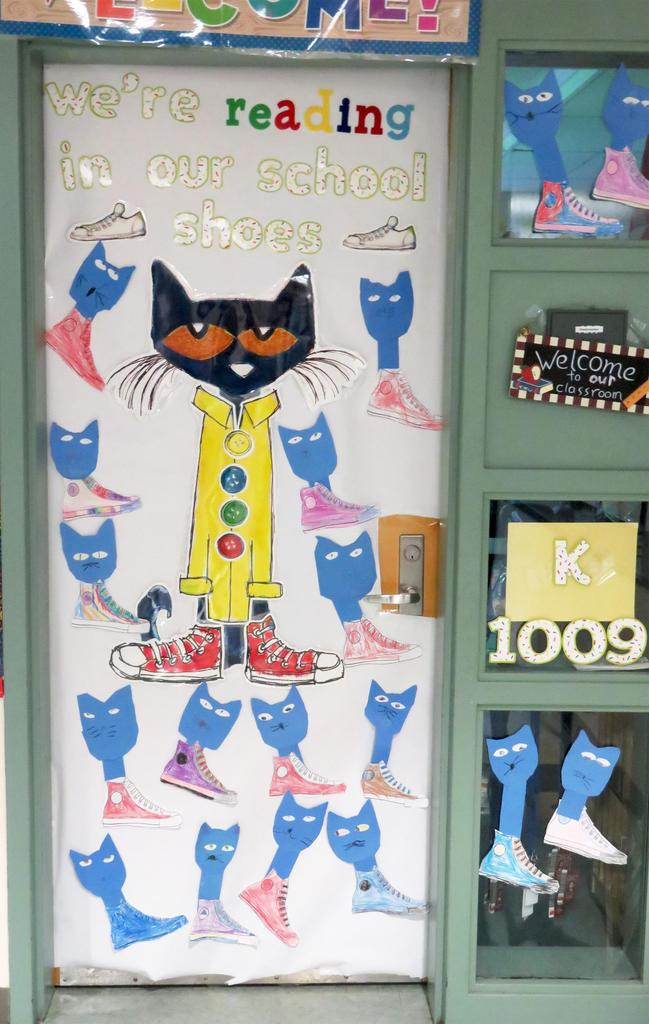 Artwork on a door, featuring cats and sneakers