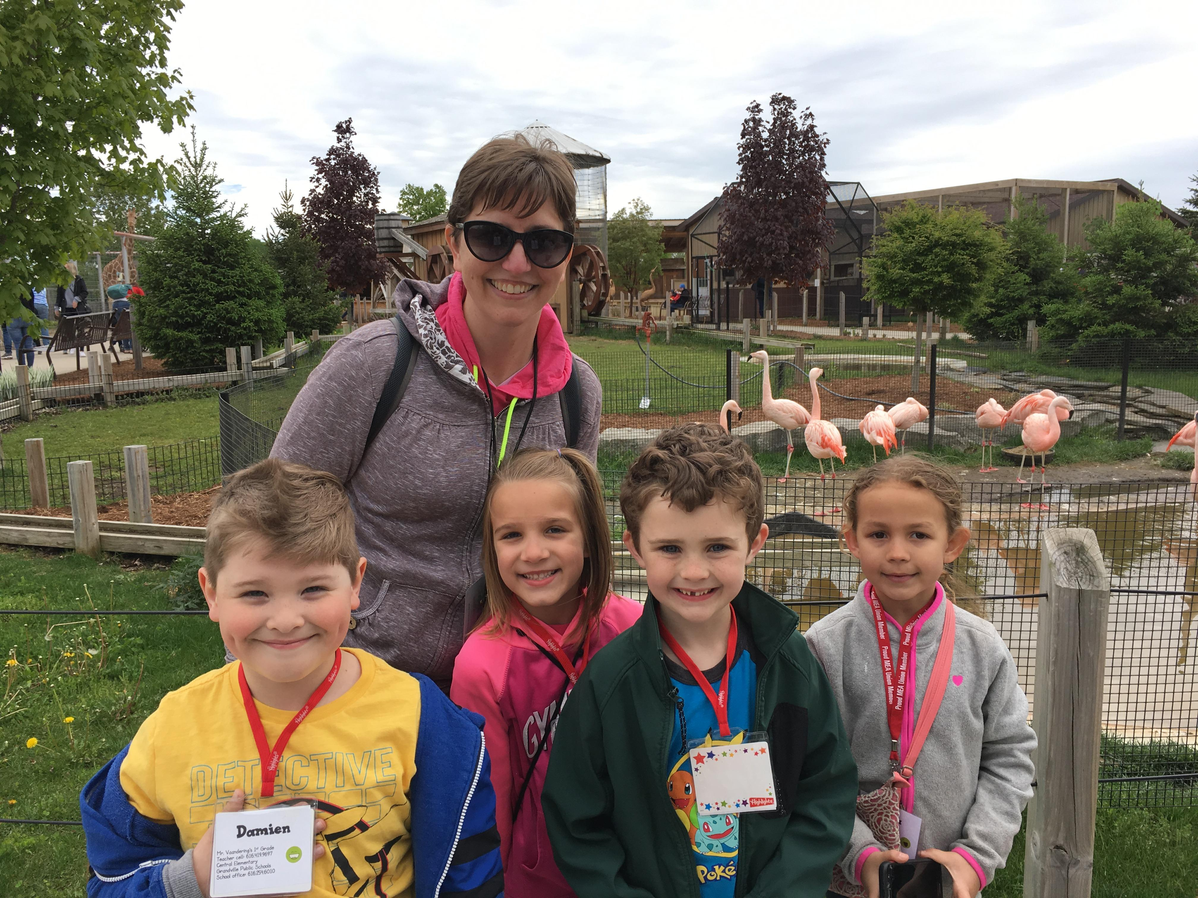 parent and 4 kids at zoo with flamingos behind them