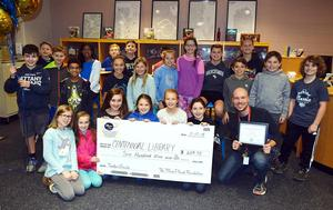 A group of students and a teacher gathered around a giant check.