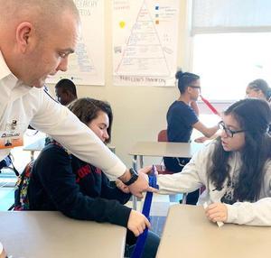 An EHS student applies a tourniquet to a classmate as an instructor gives hands-on advice