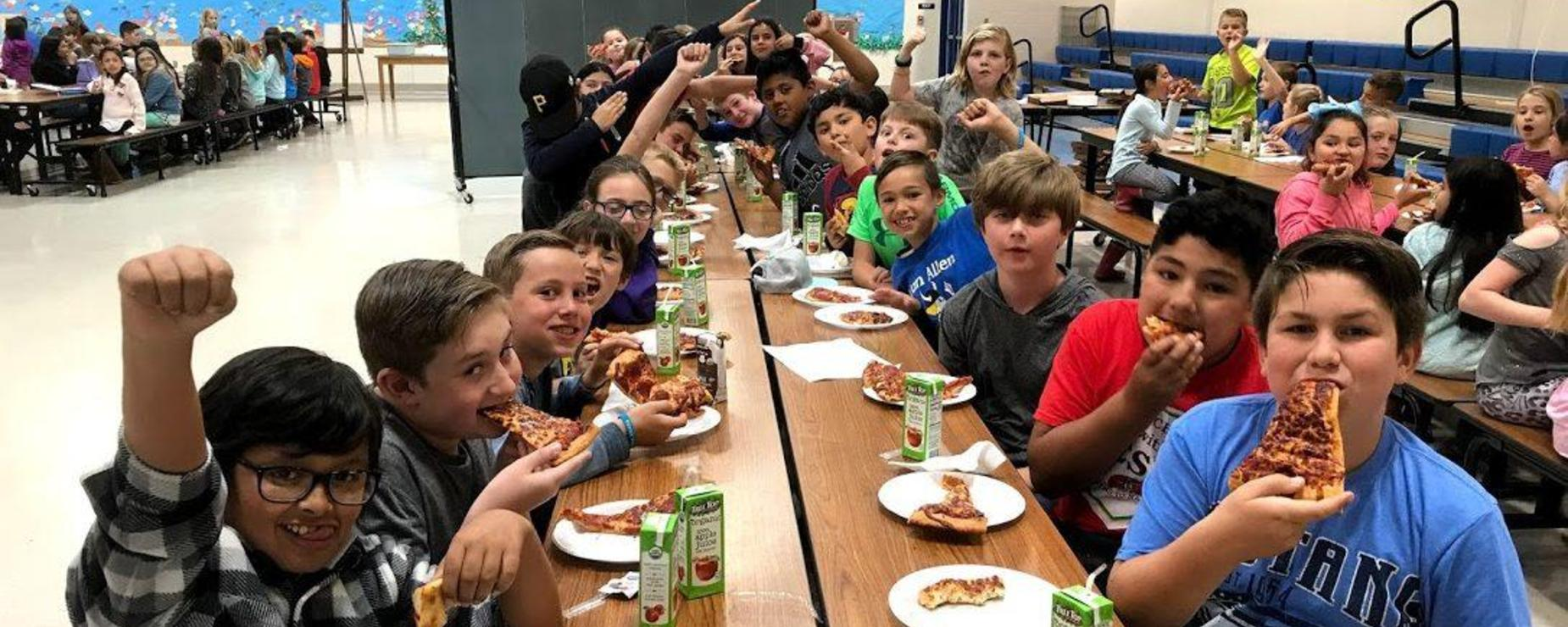 students eating pizza together in the cafeteria