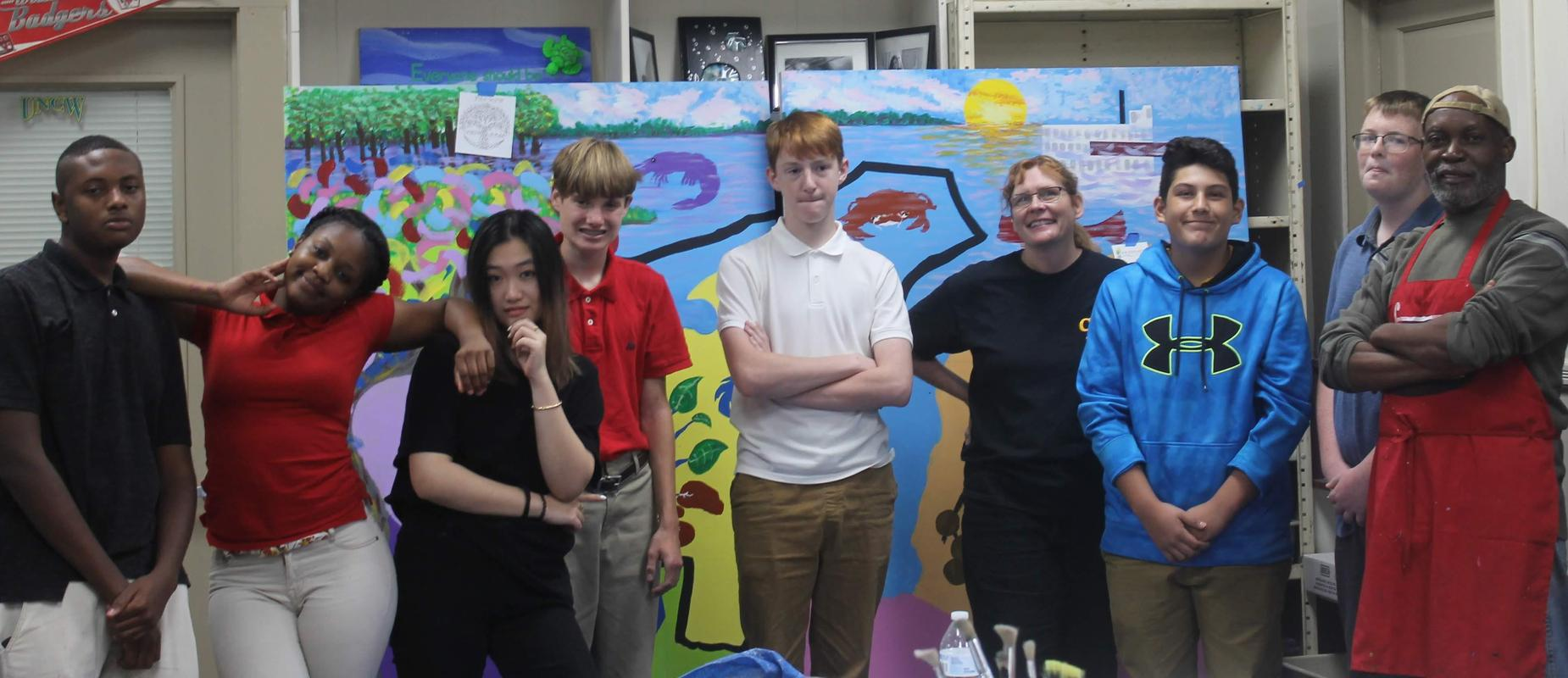 students and instructor standing in front of painted mural