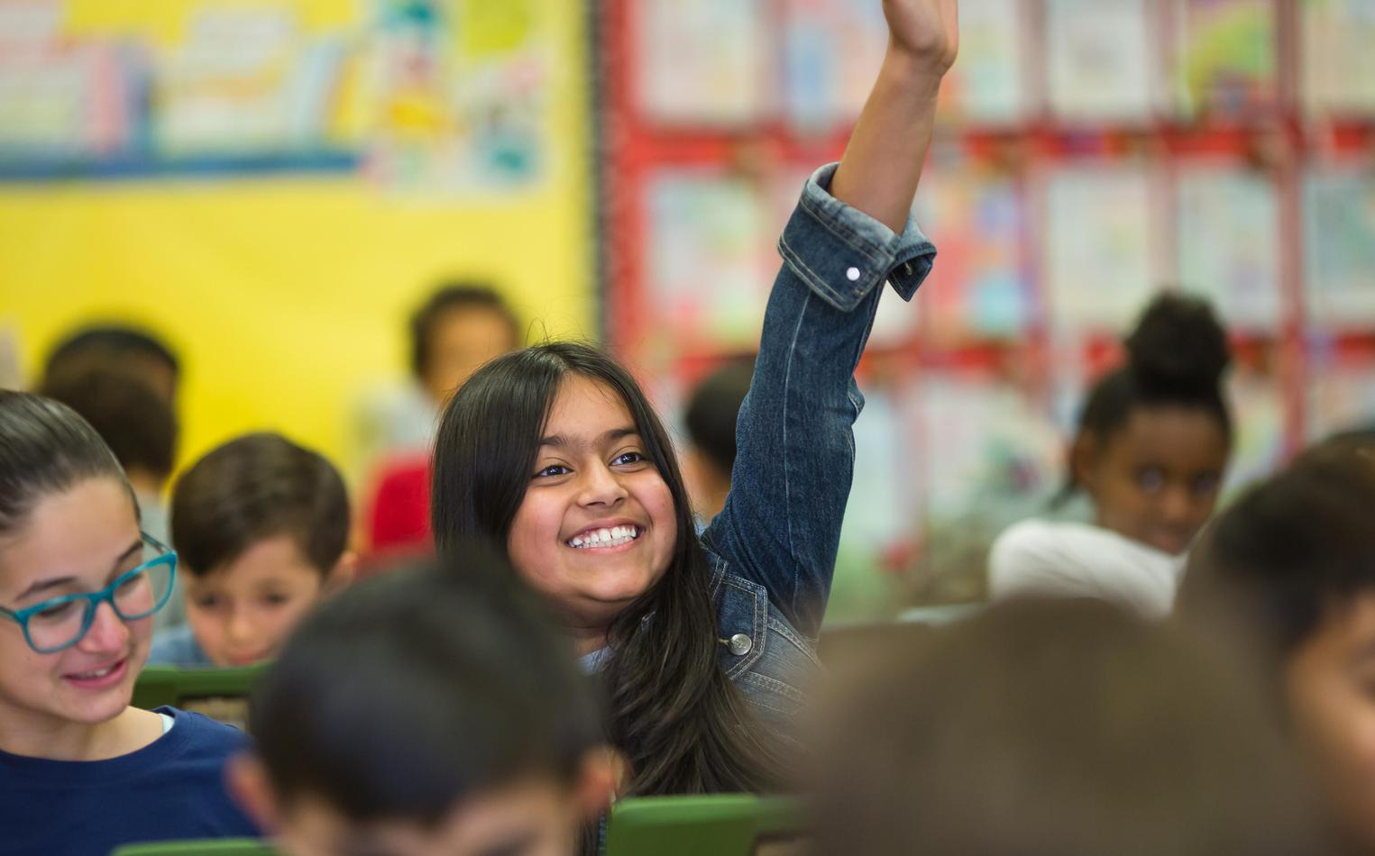 Middle school student raising her hand in class.