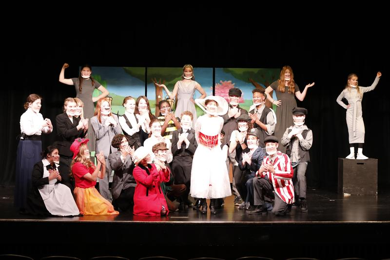 Mary Poppins Jr. still on stage with kids posed in costume